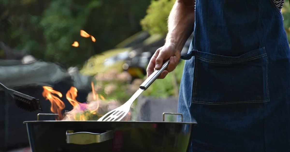 man grilling wearing an apron